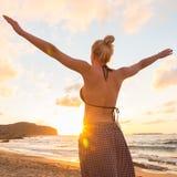 Freie glückliche Frau, die Sonnenuntergang auf Sandy Beach genießt Stockfotos