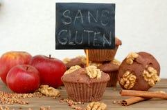 Freie Muffins des Glutens vom Buchweizen bemehlen, Apfel, cinnamonand Walnüsse auf braunem hölzernem Hintergrund mit Karteikarte  stockfotos
