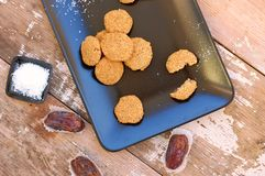 Freie Plätzchen des Glutens mit Kokosnuss und Daten am Schwarzblech auf hölzernem Hintergrund lizenzfreie stockbilder