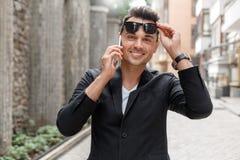 Freienfreizeit Junger Mann in der Klage und Sonnenbrille auf Stadtstraße die Sonnenbrille entfernend, die den Anruf schaut Kamera stockfotografie