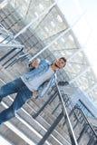 Freienfreizeit Mulattekerlstellung auf Treppe mit dem Smartphone, der oben motiviert schaut stockbilder