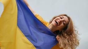 Freienporträt des Lachens des jungen Mädchens mit blauer und gelber ukrainischer Flagge in ihren Händen über dem Himmelhintergrun stock video