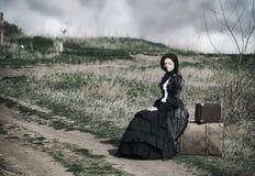 Freienporträt einer victorian Dame im schwarzen Sitzen allein auf der Straße mit ihrem Gepäck lizenzfreie stockfotos
