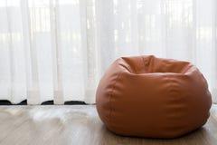 Freier Raum des links mit orange Bean-Tasche mit weißem Vorhangfenster I Lizenzfreies Stockfoto