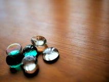 Freier Raum und Teal Mancala Glass Beads auf hölzerner Korn-Tabelle stockfotografie