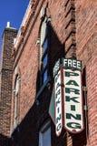 Freies Parkzeichen, das an einem alten Backsteinbau hängt Lizenzfreie Stockfotos
