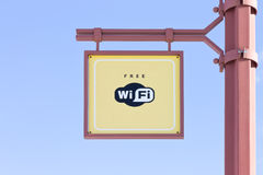 Freies WiFi - drahtloses Internet-Zeichen auf Hintergrund des blauen Himmels Lizenzfreies Stockfoto