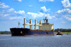 Freight Cargo Ship and Tugboat Navigating on River. Commercial seafaring carrier ship and tugboat helper navigating the calm waters of an American river after a Stock Photography