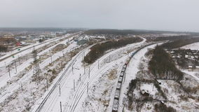 Freight, cargo train passing railroad station in winter. Aerial shoot. 4K stock footage