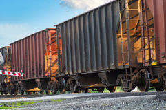 Freight cars. Rolling over a grade crossing with crossing gate lowered at left Royalty Free Stock Photography