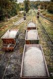 Freight cars with crushed stone on the railroad. In summer evening. Top view with semaphores on the background Stock Images