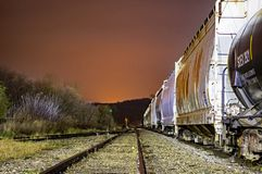 Freight Cars Idle On A Rainy Night. Freight Cars sit idle on a siding adjacent to the main tracks on an overcast, rainy night royalty free stock images