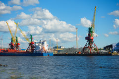 Freight cranes operate at sea vessel unloading in the port. Royalty Free Stock Photos