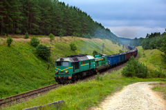 Freight diesel train. Freight train hauled by the diesel locomotives passing the forest Royalty Free Stock Images