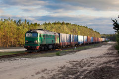 Freight diesel train. Freight train hauled by the diesel locomotive passing the forest Royalty Free Stock Image