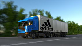 Freight semi truck with Adidas inscription and logo driving along forest road, seamless loop. Editorial 4K clip. Freight semi truck with Adidas inscription and stock video footage