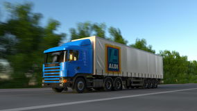 Freight semi truck with Aldi logo driving along forest road, seamless loop. Editorial 4K clip. Freight semi truck with Aldi logo driving along forest road stock video