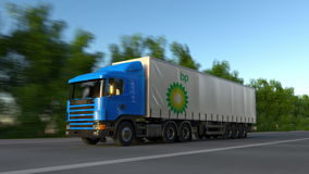 Freight semi truck with BP logo driving along forest road, seamless loop. Editorial 4K clip. Freight semi truck with BP logo driving along forest road, seamless stock footage