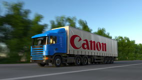 Freight semi truck with Canon Inc. logo driving along forest road, seamless loop. Editorial 4K clip. Freight semi truck with Canon Inc. logo driving along forest stock video footage