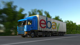 Freight semi truck with eBay Inc. logo driving along forest road, seamless loop. Editorial 4K clip. Freight semi truck with eBay Inc. logo driving along forest stock footage