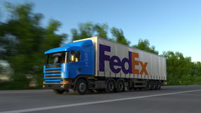 Freight semi truck with FedEx logo driving along forest road, seamless loop. Editorial 4K clip. Freight semi truck with FedEx logo driving along forest road stock video footage