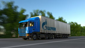 Freight semi truck with Gazprom logo driving along forest road, seamless loop. Editorial 4K clip. Freight semi truck with Gazprom logo driving along forest road stock footage