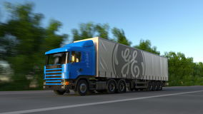 Freight semi truck with General Electric logo driving along forest road, seamless loop. Editorial 4K clip. Freight semi truck with General Electric logo driving stock footage