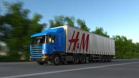 Freight semi truck with H M logo driving along forest road, seamless loop. Editorial 4K clip. Freight semi truck with H M logo driving along forest road stock video footage