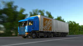 Freight semi truck with The Home Depot logo driving along forest road, seamless loop. Editorial 4K clip. Freight semi truck with The Home Depot logo driving stock video footage