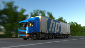Freight semi truck with HP Inc. logo driving along forest road, seamless loop. Editorial 4K clip. Freight semi truck with HP Inc. logo driving along forest road stock video footage