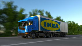 Freight semi truck with Ikea logo driving along forest road, seamless loop. Editorial 4K clip. Freight semi truck with Ikea logo driving along forest road stock video footage