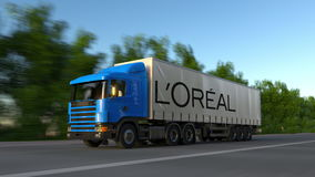 Freight semi truck with L`Oreal logo driving along forest road, seamless loop. Editorial 4K clip. Freight semi truck with L`Oreal logo driving along forest road stock video footage