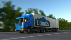 Freight semi truck with Lowe`s logo driving along forest road, seamless loop. Editorial 4K clip. Freight semi truck with Lowe`s logo driving along forest road stock video