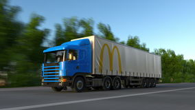 Freight semi truck with McDonald`s logo driving along forest road. Editorial 3D rendering Royalty Free Stock Photo