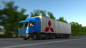 Freight semi truck with Mitsubishi logo driving along forest road, seamless loop. Editorial 4K clip. Freight semi truck with Mitsubishi logo driving along forest stock video