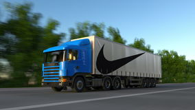 Freight semi truck with Nike inscription and logo driving along forest road, seamless loop. Editorial 4K clip. Freight semi truck with Nike inscription and logo stock video