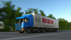 Freight semi truck with Robert Bosch GmbH logo driving along forest road, seamless loop. Editorial 4K clip. Freight semi truck with Robert Bosch GmbH logo stock footage