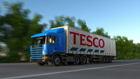 Freight semi truck with Tesco logo driving along forest road, seamless loop. Editorial 4K clip. Freight semi truck with Tesco logo driving along forest road stock video footage
