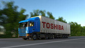 Freight semi truck with Toshiba Corporation logo driving along forest road, seamless loop. Editorial 4K clip. Freight semi truck with Toshiba Corporation logo stock video footage