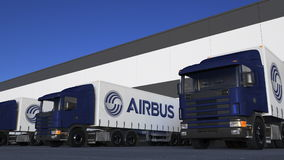 Freight semi trucks with Airbus logo loading or unloading at warehouse dock. Editorial 3D rendering. Freight semi trucks with Airbus logo loading or unloading at Royalty Free Stock Photo