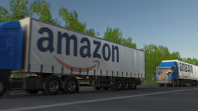 Freight semi trucks with Amazon.com logo driving along forest road. Editorial 3D rendering Stock Photo