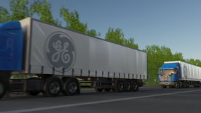 Freight semi trucks with General Electric logo driving along forest road. Editorial 3D rendering Royalty Free Stock Images