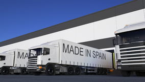 Freight semi trucks with MADE IN SPAIN caption on the trailer loading or unloading. Road cargo transportation 3D.  Royalty Free Stock Photos