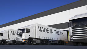 Freight semi trucks with MADE IN THE UK caption on the trailer loading or unloading. Road cargo transportation 3D.  stock images
