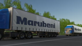 Freight semi trucks with Marubeni Corporation logo driving along forest road. Editorial 3D rendering. Freight semi trucks with Marubeni Corporation logo driving Royalty Free Stock Images