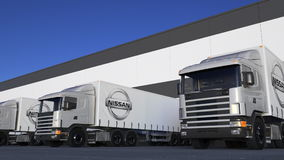 Freight semi trucks with Nissan logo loading or unloading at warehouse dock. Editorial 3D rendering. Freight semi trucks with Nissan logo loading or unloading at Stock Photos