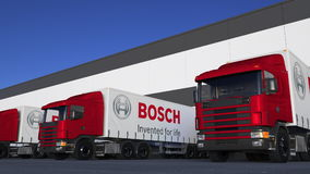 Freight semi trucks with Robert Bosch GmbH logo loading or unloading at warehouse dock. Editorial 3D rendering Royalty Free Stock Photo