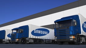 Freight semi trucks with Samsung logo loading or unloading at warehouse dock. Editorial 3D rendering Royalty Free Stock Photography