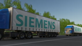 Freight semi trucks with Siemens logo driving along forest road. Editorial 3D rendering Stock Photos