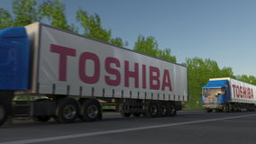 Freight semi trucks with Toshiba Corporation logo driving along forest road. Editorial 3D rendering. Freight semi trucks with Toshiba Corporation logo driving Royalty Free Stock Photo
